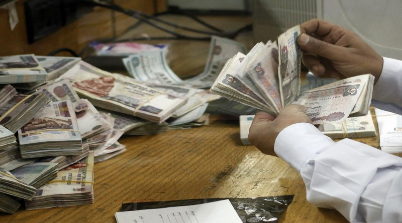 An employee counts money at a bank in Cairo